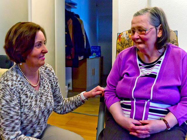 Ehrenamtliche Helferin mit älterer Dame im Rollstuhl