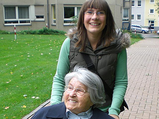 Junge Frau mit älterer Dame im Rollstuhl