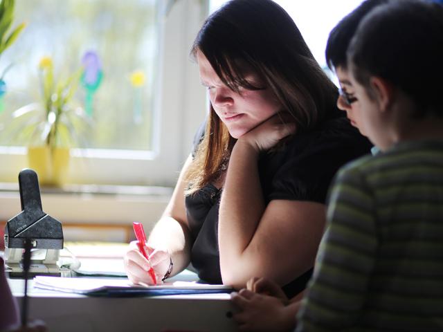 Jugendliche hilft Kindern bei den Hausaufgaben
